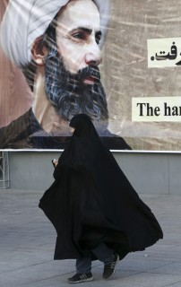 An Iranian woman walks past a portrait of Sheikh Nimr al-Nimr, a prominent opposition Saudi Shiite cleric, who was executed by Saudi Arabia last week, at the conclusion of a rally to protest his execution, in Tehran, Iran, Monday, Jan. 4, 2016. Allies of Saudi Arabia followed the kingdom's lead and began scaling back diplomatic ties to Iran on Monday after the ransacking of Saudi diplomatic missions in the Islamic Republic, violence sparked by the Saudi execution of al-Nimr. (AP Photo/Vahid Salemi)