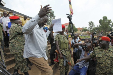 Uganda People's Defense Forces General David Sejusa is escorted by military police officers from the court martial to Luzira Prison in Kampala, Uganda, Tuesday Feb. 2, 2016.  A military general who criticized Uganda's longtime president was charged in a court-martial and remanded to jail, but his supporters said he was the victim of state persecution. Sejusa was charged Tuesday with being absent without leave, participating in political activities and insubordination. (AP Photo / Stephen Wandera)