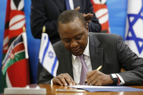 Kenya's President Uhuru Kenyatta signs an agreement after delivering joint statements with Israeli Prime Minister Benjamin Netanyahu in Jerusalem, Tuesday, Feb. 23, 2016. The two leaders signed a joint statement on water that focuses on cooperation on water and agricultural issues and establishes a joint bilateral committee. (Amir Cohen, Pool via AP)