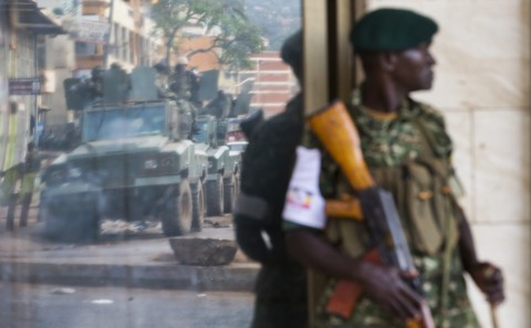 A convoy of armored personnel carriers is seen reflected in a shop window as a Ugandan soldier stands guard on a street corner, shortly after the election result was announced, in downtown Kampala, Uganda, Saturday, Feb. 20, 2016. Long-time Ugandan leader Yoweri Museveni was on Saturday declared the winner of the country's disputed presidential election, but the main opposition party rejected the results as fraudulent and called for an independent audit of the count. (AP Photo/Ben Curtis)