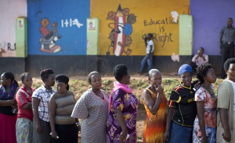 Ugandans queue to cast their votes outside a polling station located at a school in Kampala, Uganda, Thursday, Feb. 18, 2016. Ugandans went to the polls Thursday as President Yoweri Museveni, in power for 30 years, is facing his tightest race ever with opposition leader Kizza Besigye his main challenger. (AP Photo/Ben Curtis)