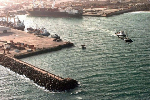 "Aerial view of the Port of Mogadishu.  Three cargo ships, large, medium and small sized vessels are moored to the docks.  A tugboat is heading out of the port.  A US Marine UH-1N ""Huey"" helicopter flies left to right at the right of the frame.  The port played an important role in the support of Operation Restore Hope."